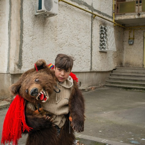 A boy wearing a natural bear skin and mask poses in front of a communist block of flats in South Bucharest, Piata Sudului. He is part of a bigger group of 20 youngsters, which came from the Bacau area (300 km away from Bucharest), countryside, to perform the Bear Dance. This old ritual, which is losing its track in the pagan period symbolizes the death and the rebirth of the bear, which is link with the New Year Eve and harvest.