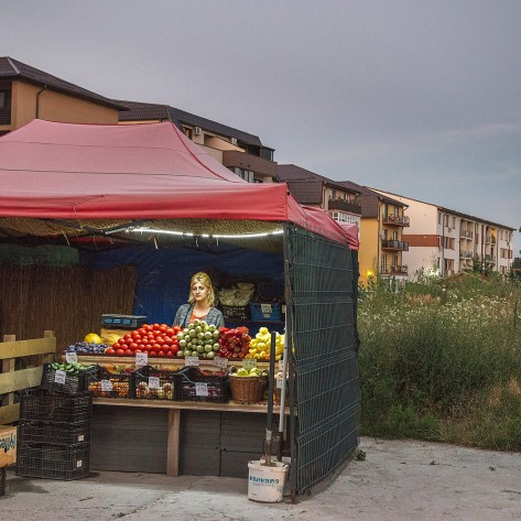 Elena, a vegetable seller in a newly built residential quarter in Rosu, Bucharest. Formerly a village within the capital borders, Rosu was a village of farmers which provided vegetables in the city market. Now, as their houses and land is sold to construct bigger things, the vegetables are coming mostly from imports (Turkey).