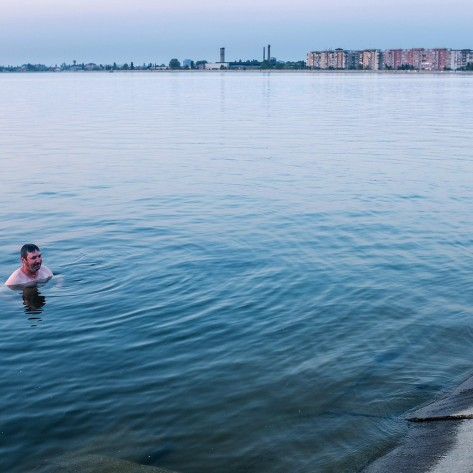 """A man which is doing that each afternoon after he finishes his jobs, baths in the Morii Lake. """"The water is clear, the temperature's perfect. This is how i get rid of my black toughs"""" The lake was built by the communists in the 80's to protect the city against floods. Back then, cement was poured over a decommisionned residential area, which included a cemetery and a Church. From this reason, the locals consider the lake cursed, although many, lacking other opportunities, are swimming in its dirty waters or sun bathing nearby."""
