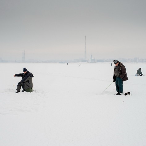 People are ice fishing on the frozen surface of the larges artificial lake in Bucharest, Lacul Morii. The lake was built by the communists in the 80's to protect the city against floods. Back then, cement was poured over a decommisionned residential area, which included a cemetery and a Church. From this reason, the locals consider the lake cursed, although many, lacking other opportunities, are swimming in its dirty waters or sun bathing nearby.
